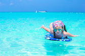 Little girl swimming on a surfboard in the turquoise sea — Stock Photo