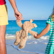 Close up bunny toy in the hands of daughter and dad on sea background — Stock Photo