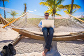 Businessman sitting in hammock using laptop during summer vacation — Stock Photo