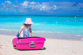 Little adorable girl with big colorful suitcase and a map on tropical beach — ストック写真