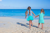Two little cute girls enjoy their summer vacation on the beach — Stock Photo