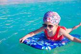 Petite fille adorable sur une planche de surf dans la mer turquoise — Foto de Stock