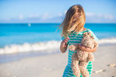 Adorable little girl with her favorite toy on tropical beach vacation — Stock Photo