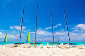 Group of catamarans with colorful sails on exotic Caribbean beach — Stock Photo