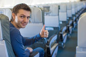 Happy man showing thumbs up inside the aircraft — Stock Photo