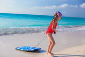 Little adorable girl pulls a surfboard on white shore — Stock Photo