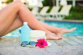 Suncream, hat, sunglasses, flower and tanned female legs near pool — Foto Stock