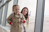 Mother and little daughter near the window at airport terminal — Stock Photo