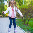 Adorable little girl on roller skates in the park — Stock Photo