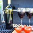 Two glass of red wine, steak and tomatoes on barbecue outdoors — Stock Photo #46179585