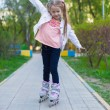 Little adorable girl on roller skates in the park — Stock Photo