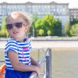 Little adorable girl on the deck of a ship sailing in big city — Stock Photo #46179861