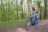 Mother and little daughter cycling bicycle at the park — Stock Photo