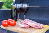 Two glass of red wine, steak and tomatoes on barbecue outdoors — Photo