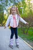 Adorable little girl on roller skates in the park — Foto Stock