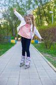 Roller üzerinde küçük sevimli kız parkta kaymaktadır — Stok fotoğraf