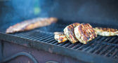T-bone steak cooking on an open flame grill — Stock Photo