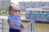 Little cute girl relaxing on a luxury ship sailing in the big city — Stock Photo