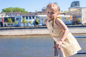 Little adorable girl on the deck of a ship sailing in big city — Stock Photo