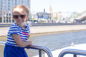 Little happy girl relaxing on a luxury ship sailing in the big city — Stock Photo