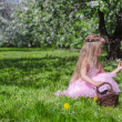 Cute little girl picking flowers in blossoming apple orchard at sunny day — Stock Photo
