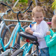 Little adorable girls having fun near the bikes on exotic resort — Stock Photo