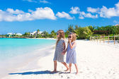 Little adorable girls on white beach walking by the sea — Foto de Stock