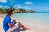 Young man in santa hat with phone on tropical caribbean beach — Stock Photo