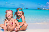 Little girls in glasses for swimming playing with the sand on summer vacation — Stock Photo
