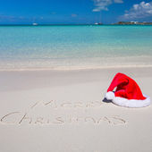 Santa Hat on white sandy beach and Merry Christmas written in the sand — Foto de Stock