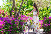 Young beautiful woman on vacation biking at lush garden — Stock Photo