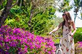 Young beautiful woman riding a bike at flowering garden — Stock Photo