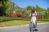 Young woman riding a bike on tropical resort — Stock Photo