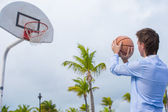 Young man playing basketball outside at exotic resort — 图库照片