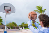 Young man playing basketball outside at exotic resort — Stok fotoğraf