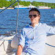 Young man swiming and resting on his yacht at sunny day — Stock Photo