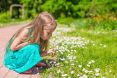Portrait of adorable little girl blowing a dandelion in the park — Stock Photo