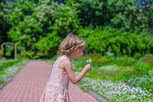 Feliz niña sopla un diente de león en el parque de floración — Foto de Stock