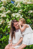 Young mother and her lovely daughter whispering on the bench — Stock Photo