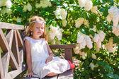 Adorable happy little girl in flower blossoming garden — 图库照片