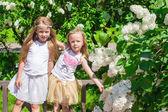Little happy girls enjoy weekend in beautiful blooming garden — 图库照片