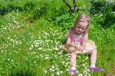 Little adorable girl on flower green glade — 图库照片