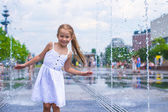 Little happy girl have fun in street fountain at hot sunny day — Stock Photo