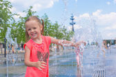 Little adorable girl have fun in street fountain at hot sunny day — Foto Stock