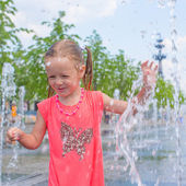 Little adorable girl have fun in street fountain at hot sunny day — 图库照片