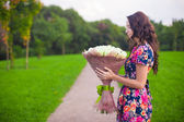 Beautiful young woman with big bouquet of white roses — Stock Photo