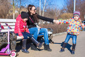 Young mother and little happy girls enjoy sunny day in the park — Stock Photo