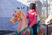 Little adorable girl on carousel at sunny day outdoor — Stock Photo