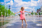 Little happy girl playing in open street fountain at hot sunny day — Stock Photo