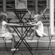Little happy girls have fun at outdoor cafe — Stock Photo #47582511
